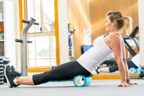 A woman using an exercise roller in front of a mirror in a gym