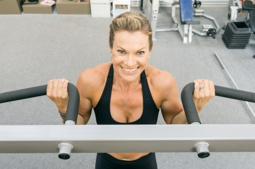 A close up of a fit womans face doing chin ups in a gym