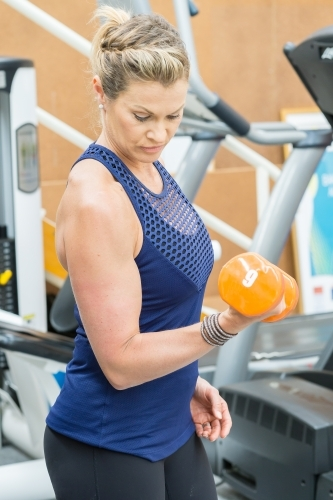 A fit woman lifting weights in a gym