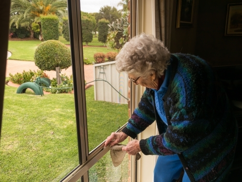 Older lady cleaning a window which looks out to a garden