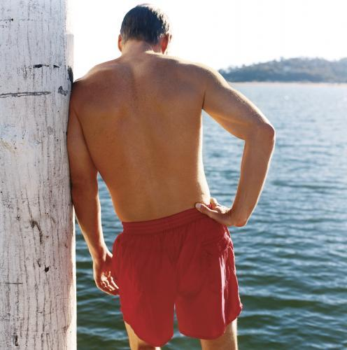 Shirtless man standing on wooden pier looking at water