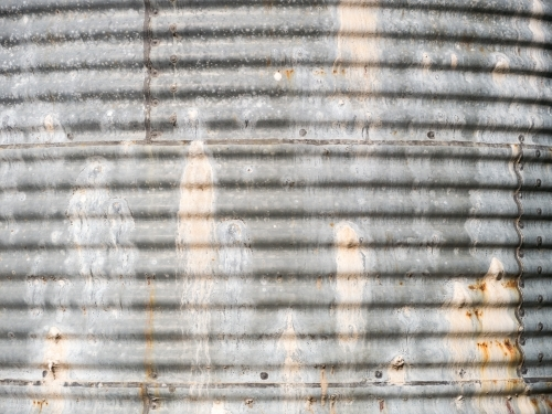 Side of an old, leaky corrugated iron water tank