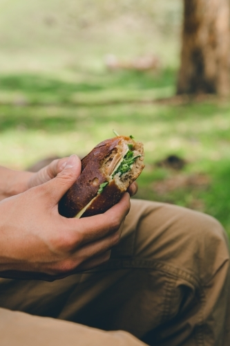 Side view of a man eating a bread roll sandwich, sitting in a green park