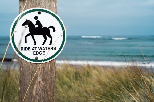 Sign instructing horse riders at beach entrance