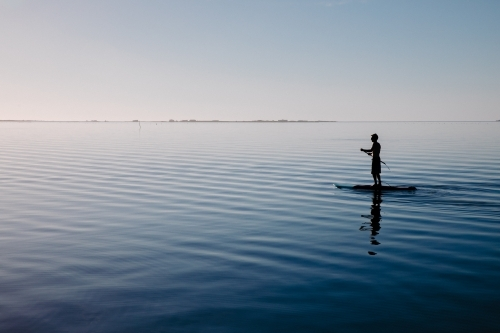 Silhouette of a man on a stand-up paddle board on very still water