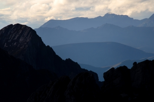 Silhouette of a mountain at the front of a mountain range