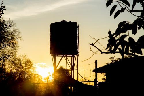Silhouette of a rain water tank on a stand at sunset