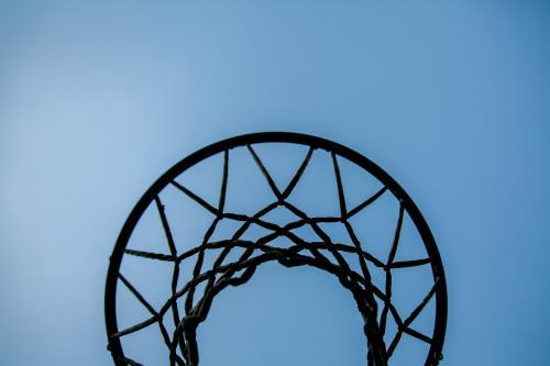 Silhouette of basketball hoop and net against blue sky