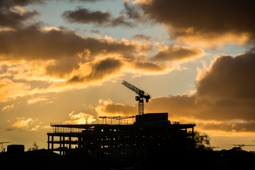 Silhouette of building site at sunset