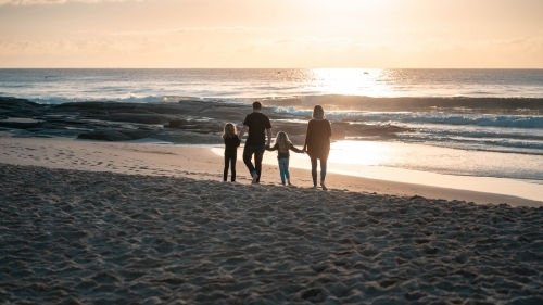 Silhouette of family walking into sunrise