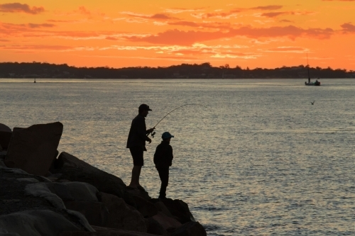 Silhouette of father and son fishing off breakwall at sunset