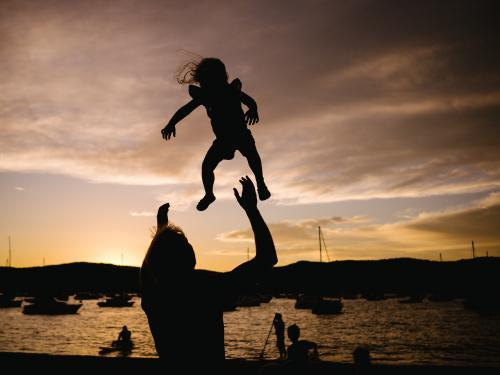 Silhouette of father throwing daughter into the air at sunset