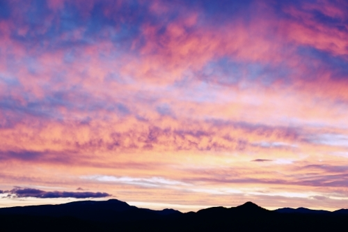Silhouette of mountains under a dramatic sky at sunset.