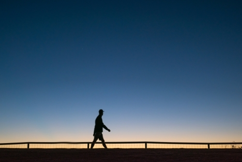 Silhouette of person walking along walkway at dawn.