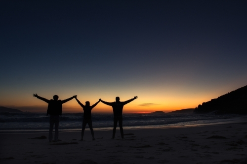 Silhouette of three friends holding hands raising against a sunset background