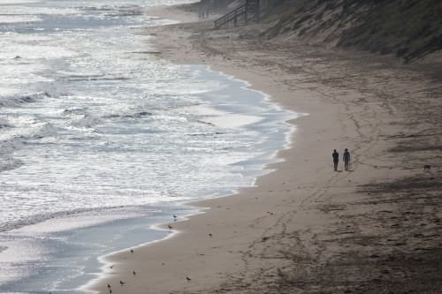 Silhouette of two distant people walking along a beach