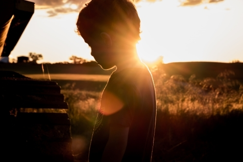 Silhouette of young boy & machinery, rural farming property in background as sun setting