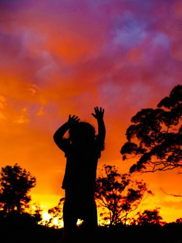 Silhouette of young child reaching up to sky at sunset