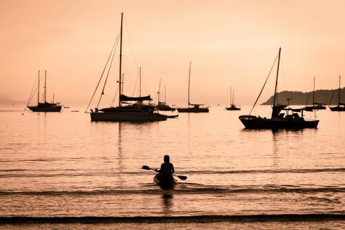 Silhouetted boats and person kayaking on a calm morning off Airlie Beach