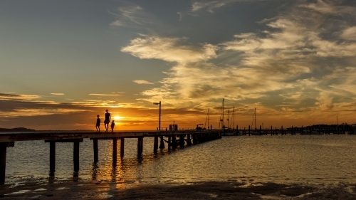 Silhouetted mother & her 2 daughters walking along wooden jetty at sunset