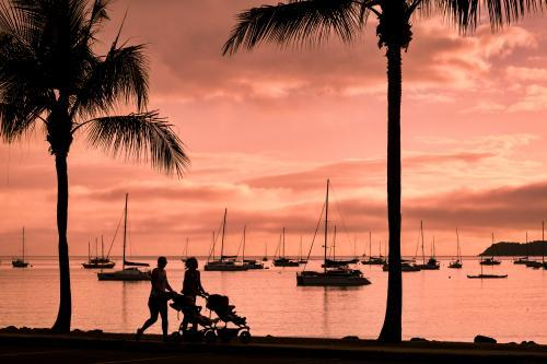 Silhouetted strollers with yachts in background at sunset on Airlie Beach.