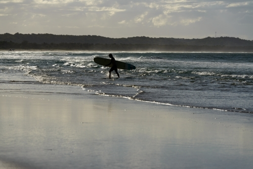 Silhouetted surfer walking out of the water carrying his board with glistening water