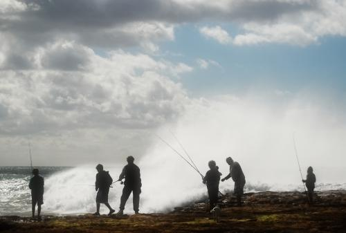 Silhouettes of people fishing off the beach with big waves