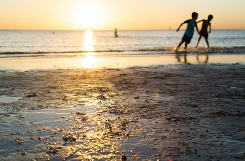 Silhouettes of two young boys playing at the beach at sunset