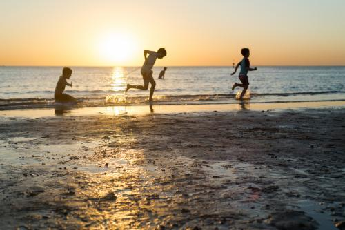 Silhouettes of three young boys playing at the beach at sunset