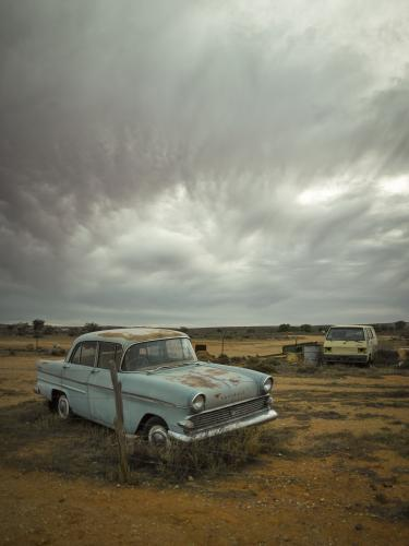 Rusted out blue car in the outback against dramatic sky