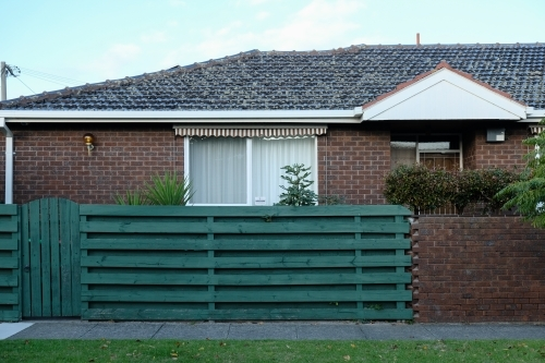 Single storey brick house with green fence
