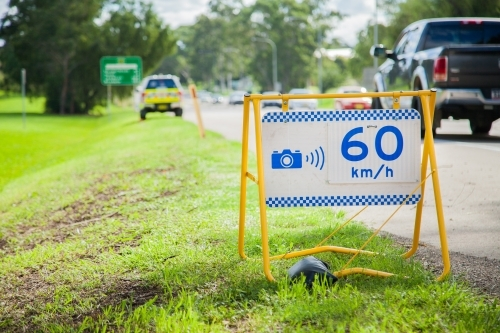 Police speed camera 60 km speed zone sign beside highway