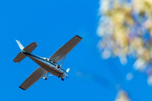 small aeroplane flying over against blue sky