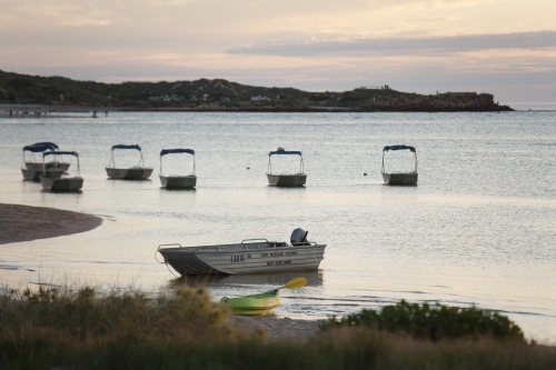 Small boats in harbour at sunset