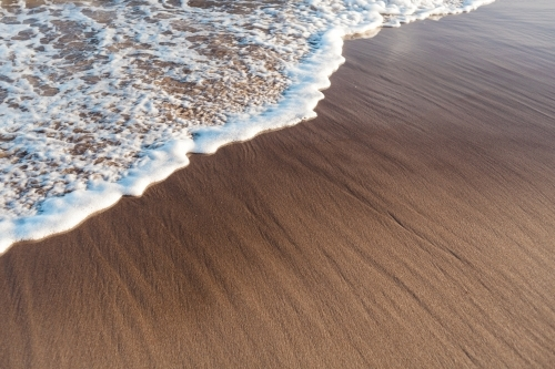 Small, foamy wave washes in against wet textured sand.