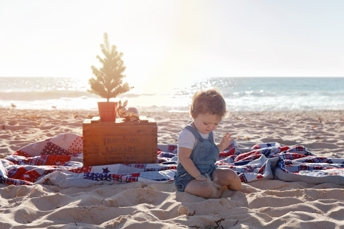 Small Girl Sitting In a Christmas Themed Setting At The Beach At Sunset