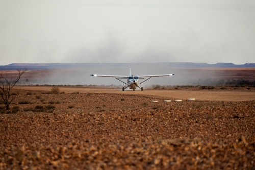 small plane landing on dirt airstrip
