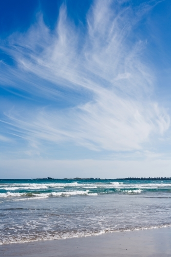small waves breaking on a beach under a big sky