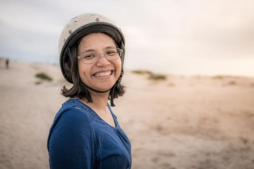 Smiling Asian mother ready to ride camels on beach at sunset