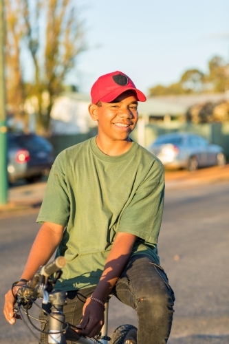 smiling boy looking at camera resting on bike