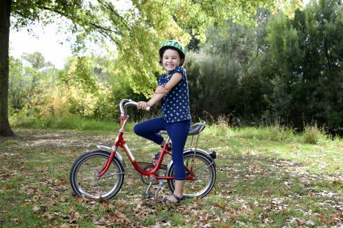 Smiling girl wearing helmet with red bike