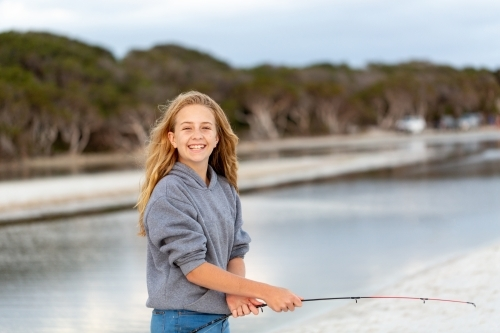 Smiling happy girl on beach in front of water with fishing rod