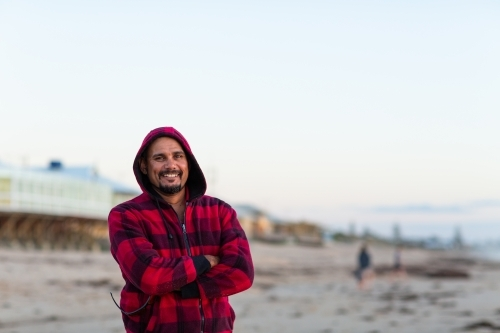 Smiling indigenous man standing with arms crossed in red checked hoody