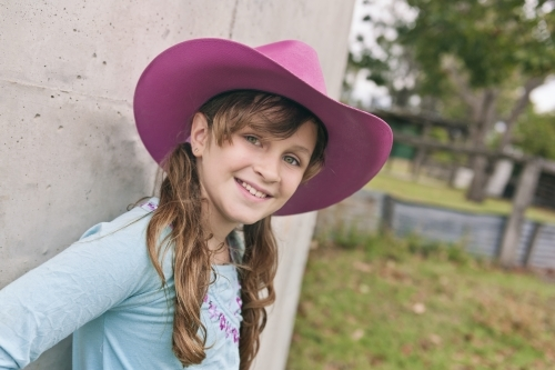 Smiling tween girl in a pink cowgirl hat