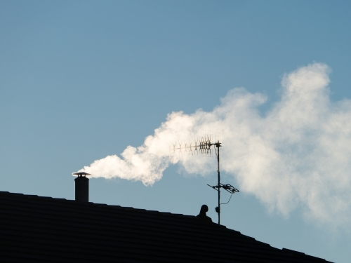 Smoke billowing from a chimney through a TV aerial against a blue sky