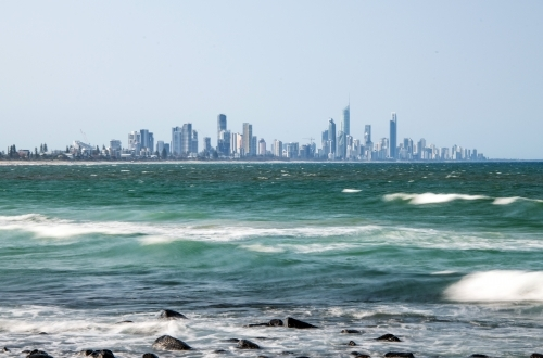 Smooth waves over the ocean with the Gold Coast skyline in the distance