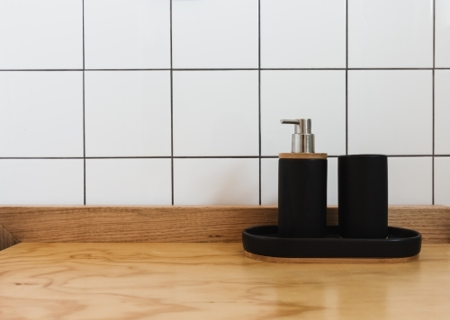 Soap dispenser and tub in black on a wooden vanity in a renovated bathroom