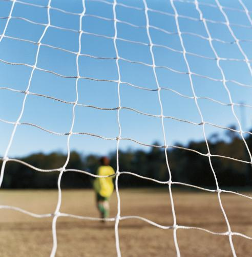 Soccer Football net with blurry goal keeper