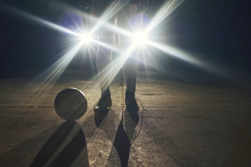 Soccer player standing in front of headlights at night