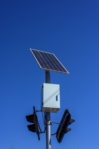 Solar panel powered traffic light against blue sky background, clean energy in use